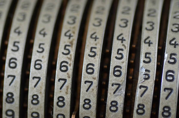 Numbers in focus on the wheel of a mechanical calculator - copyright https://www.flickr.com/photos/grandmaitre/